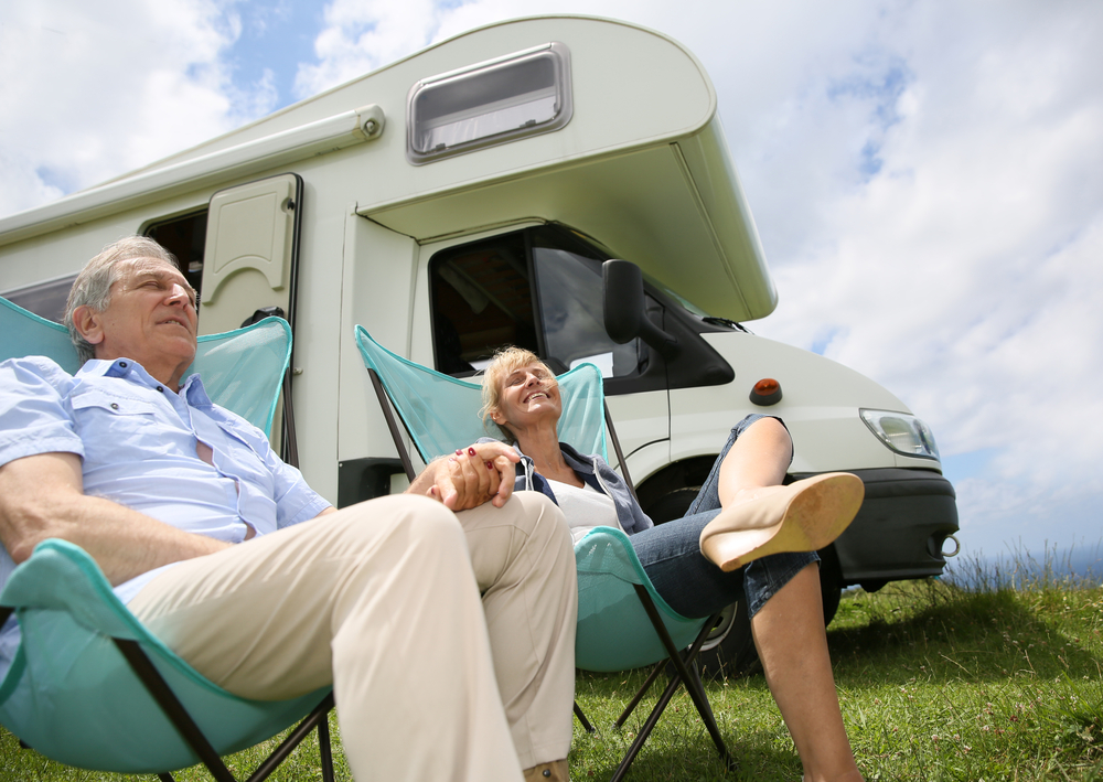 Senior couple relaxing in camping folding chairs, camper in background-2