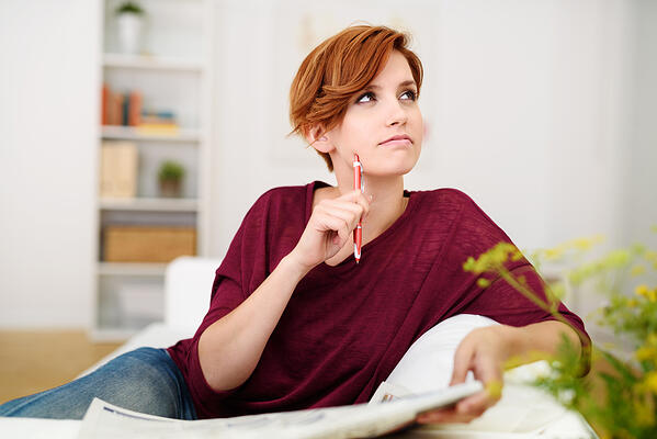 Thoughtful Attractive Young Woman Answering Crossword Puzzle Game on Newspaper at the Living Room Couch.-1